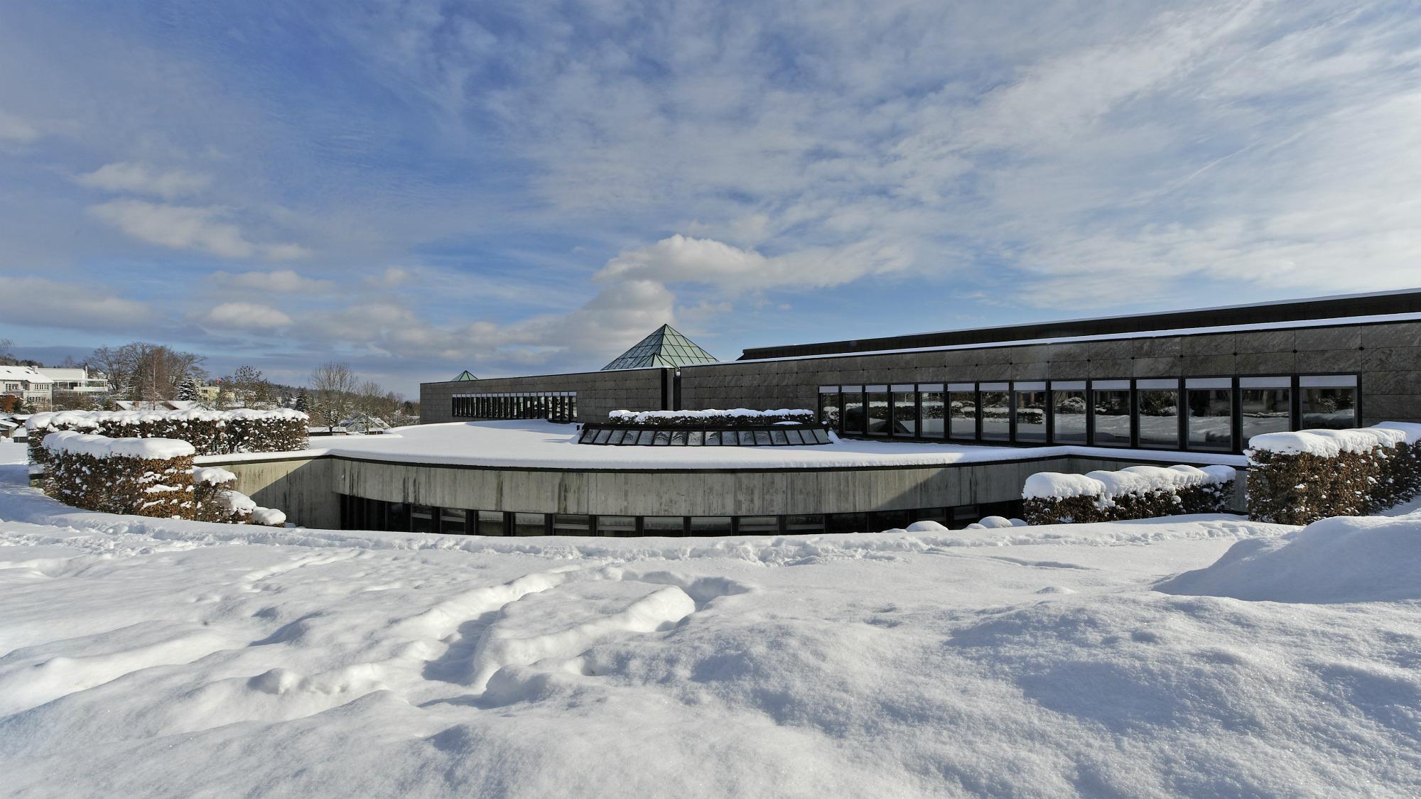 Stimmungsbild Universitaet St.Gallen (HSG): Bibliotheksgebaeude mit Schnee bedeckt, blauer Himmel und ein ein paar Wolken